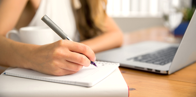 Close up of woman writing with pen on pad