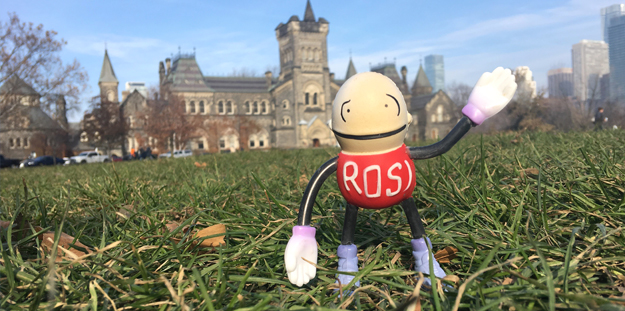 Small ROSI doll waves on grass in front of University College