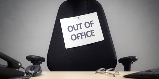 Empty office chair with sign that says Out of Office