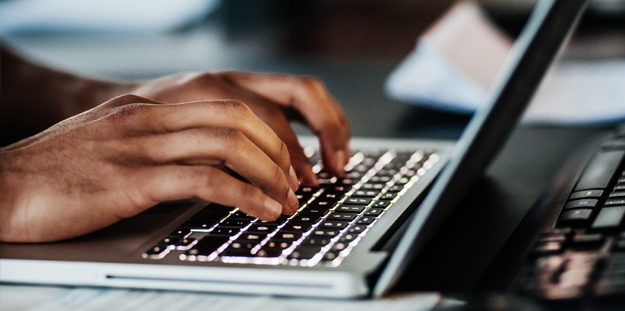 Close up of man's hands typing on laptop