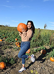 Moulika posing in a pumpkin patch while holding a pumpkin and smiling